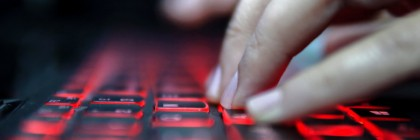Teenage Hacker Girl Attacks Corporate Servers in Dark, Typing on Red Lit Laptop Keyboard. Room is Dark